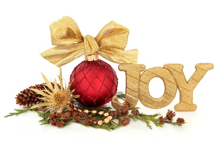 flora: Christmas joy glitter sign with red sparkling bauble and bow, gold thistle flower head, bead strand, cedar leaf sprigs and pine cones over white background  Stock Photo
