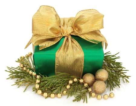 gold chain: Christmas gift box in green with gold bow, bead chain and bauble cluster with glitter fauna over white background