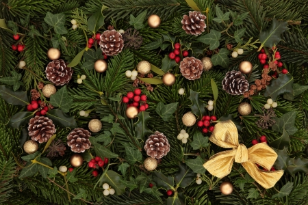 Festive background of holly, mistletoe and ivy leaf springs with blue spruce, pine cones, gold bow and bauble arrangement  Stock Photo - 15476559
