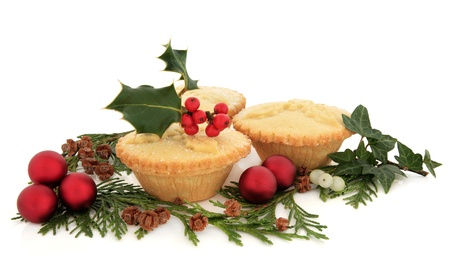 mince pie: Christmas mince pie group with holly, ivy, cedar leaf sprigs, mistletoe and red bauble decorations over white background  Stock Photo