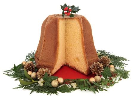 weihnachtskuchen: Pandoro Weihnachtskuchen mit Stechpalme, gold bauble Clustern, Mistel, Efeu, Tannenzapfen und Zeder Zypresse Blattfeder Dekorationen auf weißem Hintergrund Lizenzfreie Bilder