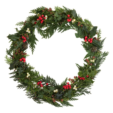 pine wreath: Christmas decorative wreath of holly, ivy, mistletoe, cedar and leyland leaf sprigs with pine cones over white background