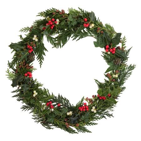 muerdago: Navidad decorativos corona de acebo, hiedra, muérdago, las ramitas de cedro y hoja leyland con conos de pino sobre fondo blanco