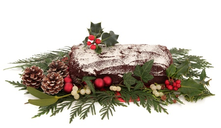 Yule log chocolate christmas cake with flora decoration of  holly, ivy, mistletoe and cedar cypress leaf sprigs with pine cones and red bauble clusters over white background  photo