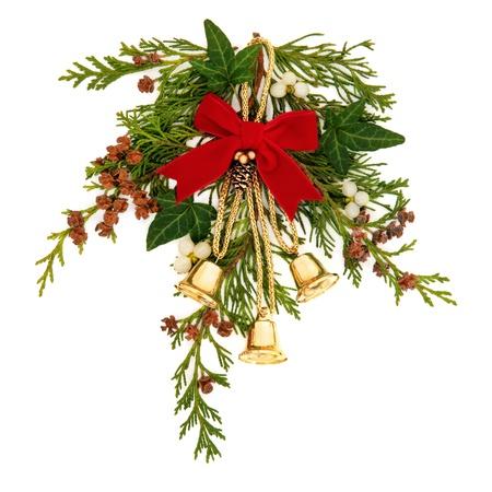 campanas: Aerosol decorativo de Navidad de muérdago, hiedra, ramitas de hojas de cedro con conos de pino y campanas de oro atadas con una cinta de terciopelo rojo sobre fondo blanco