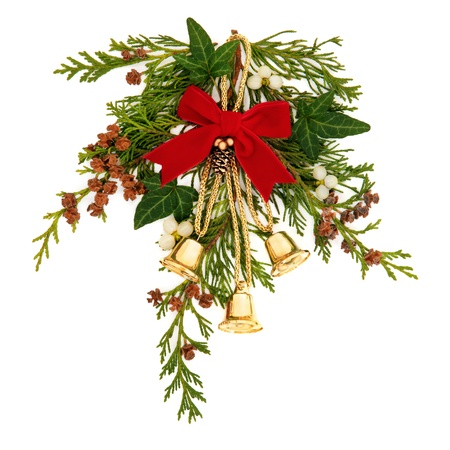 Christmas decorative spray of mistletoe, ivy, cedar leaf sprigs with pine cones and golden bells tied with a red velvet ribbon over white background