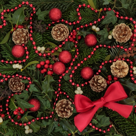 Christmas background decoration of holly, mistletoe and ivy leaf springs with blue spruce, pine cones and red bow and bauble arrangement  Stock Photo - 15572762
