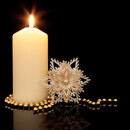 Christmas decoration of gold bead chain, snowflake sparkling bauble and lit candle with holder over black background Stock Photo - 15572735