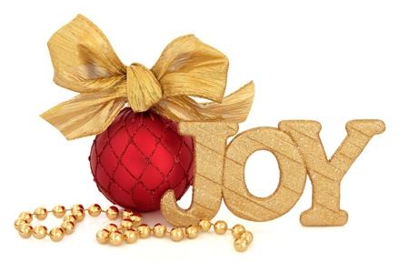 Christmas joy golden glitter sign, red bauble with gold bow and bead chain over white background  photo