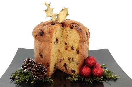 Panettone christmas cake with gold holly leaves on a black plate with red bauble cluster, pine cone and gold tipped leaf sprigs over white background