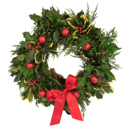 wreath: Christmas decorative wreath of holly, ivy, cedar cypress leaf sprigs and red bauble decorations with bow over white background