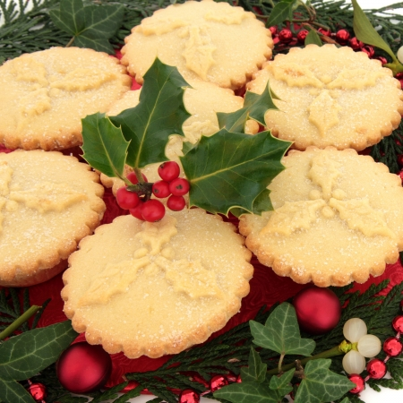 minced pie: Christmas mince pie group with holly surrounded by ivy and cedar leaf sprigs, mistletoe, red bauble and bead decoration over white background  Stock Photo