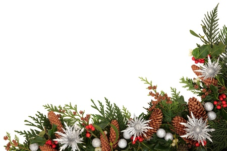 christmas ivy: Christmas decorative border of holly, ivy, mistletoe, cedar leaf sprigs with pine cones, silver baubles and thistle sprays, emblem of scotland over white background  Stock Photo