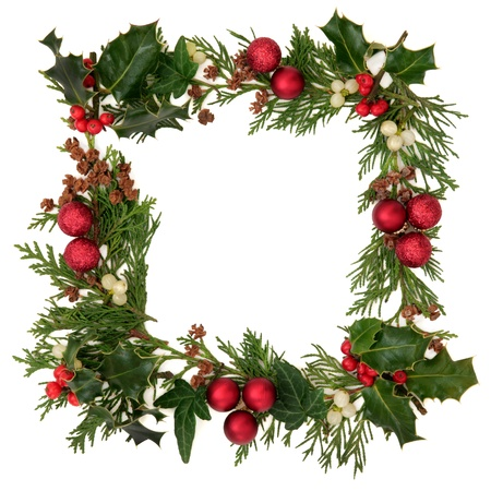 christmas ivy: Christmas decorative border of holly, ivy, mistletoe, cedar leaf sprigs with pine cones and red baubles over white background