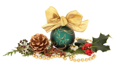 Christmas green sparkling bauble with bow surrounded by holly, mistletoe, ivy and cedar leaf sprigs with gold pine cones and bead chain over white background Stock Photo - 15799749