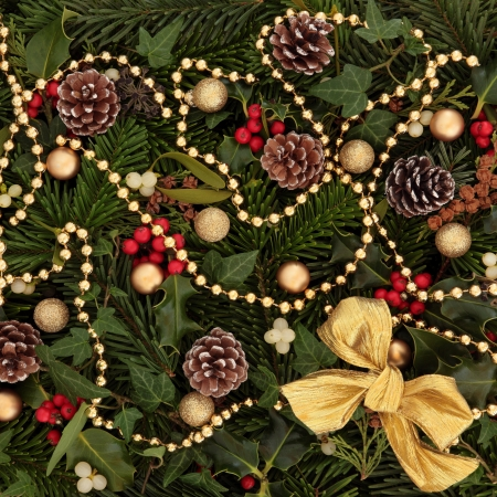 Festive background of holly, mistletoe and ivy leaf springs with blue spruce, pine cones, gold bow, bead and bauble arrangement Stock Photo - 15799757