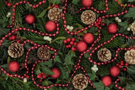 Christmas background of holly, mistletoe and ivy leaf springs with blue spruce, pine cones, red bauble and bead arrangement  Stock Photo - 15799758
