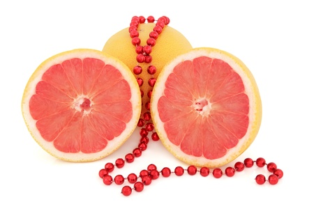 Ruby red grapefruit whole and in half with strand of beads over white background  Stock Photo - 16100822