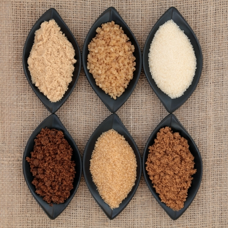 Selection of demerara, granulated, molasses, muscovado, crystal and light brown sugar in black  bowls over hessian background    Stock Photo - 16100834