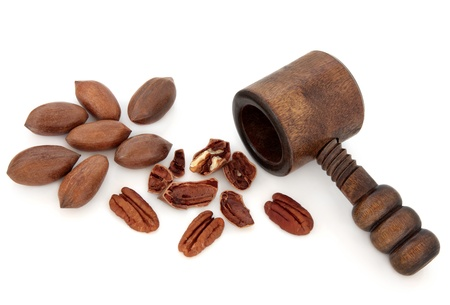 Pecan nuts with an old wooden nutcracker over white background Stock Photo - 16100813
