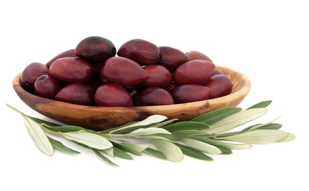 kalamata: Olives in an olive wood bowl with leaf sprigs over white background
