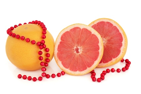 Ruby red grapefruit whole and in half with strand of beads over white background Stock Photo - 16244200