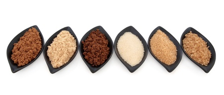 granulated: Selection of muscovado, light brown, molasses, granulated, demerara and crystal sugar in leaf shaped black bowls over white background  Stock Photo