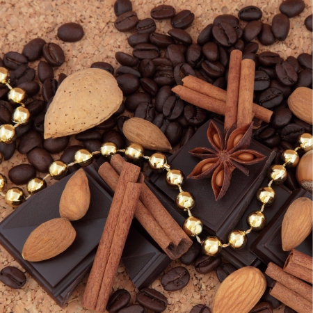 Dark chocolate, coffee beans, almonds and hazelnuts, star anise and cinnamon stick spice draped with a gold bead chain over natural cork background  photo
