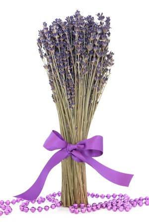 Lavender herb flower bundle tied with a purple satin ribbon with loose bead strand over white background Stock Photo - 16244207