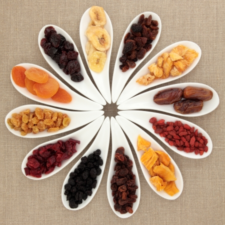 Large dried fruit selection in white porcelain dishes over beige linen background  Stock Photo