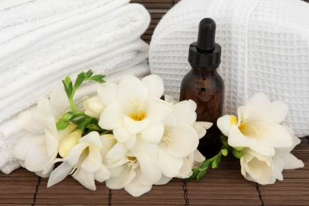Freesia flower arrangement with aromatherapy essential oil bottle with white spa towels and linen sponge over bamboo background  Stock Photo - 16383864