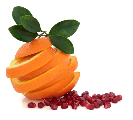 Pomegranate seed and sliced orange fruit with leaf sprig over white background  Stock Photo - 16383853
