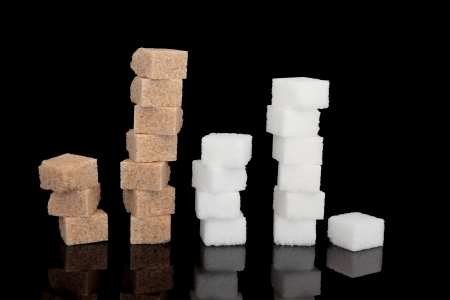 Brown and white sugar cube  stacks over black background Stock Photo - 16383855