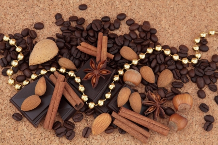 Dark chocolate, coffee beans, almonds and hazelnuts, star anise and cinnamon stick spice draped with a gold bead chain over natural cork background Stock Photo - 16383868