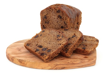 speciality: Bara brith fruit cake on an olive wood board over white background, welsh speciality