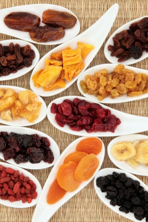 Dried fruit selection in white porcelain dishes over wicker background Stock Photo - 16383867