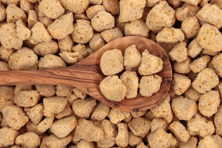 Soy protein chunks in an olive wood spoon and forming a background  Stock Photo - 17119328