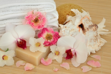Spa accessories with pink rose, white orchid and syringa flowers with natural soap, shell, sponge and towels over bamboo  Stock Photo - 17119333