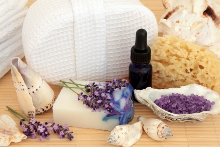 Spa still life of lavender flower herb sprigs, handmade soap, aromatherapy oil, sponge, bath crystals and sea shells over bamboo Stock Photo - 17119332