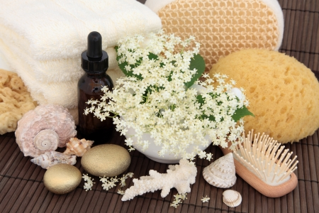 Elderflower flowers with leaf sprigs, aromatherapy essential oil bottle, gold spa stones, cream towels, exfoliating scrub, natural sponges and brush over bamboo Stock Photo - 17119674