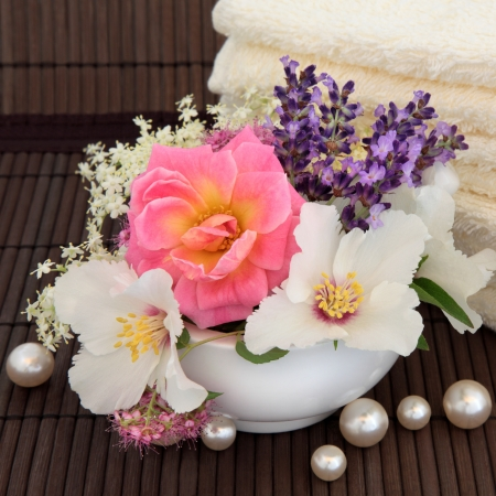 Rose, syringa, elderflower, spirea and lavender herb flower blossom with cream towels and loose pearls over bamboo background Stock Photo - 17119658