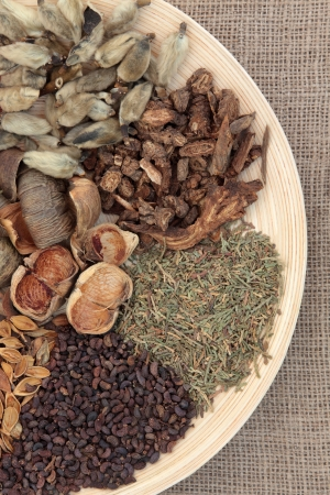 Chinese traditional herbal medicine selection on a round wooden bowl over hessian backgorund  Stock Photo
