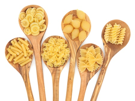 Pasta varieties of macaroni, messicani, farfalline, conchiglie, farfalle and fusilli in olive wood spoons over white background  Stock Photo - 17119666