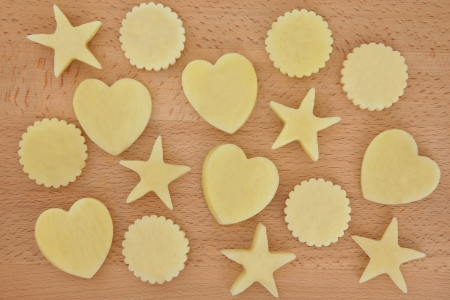 Raw potato heart, circle and star shapes over beech wood background Stock Photo - 17119331