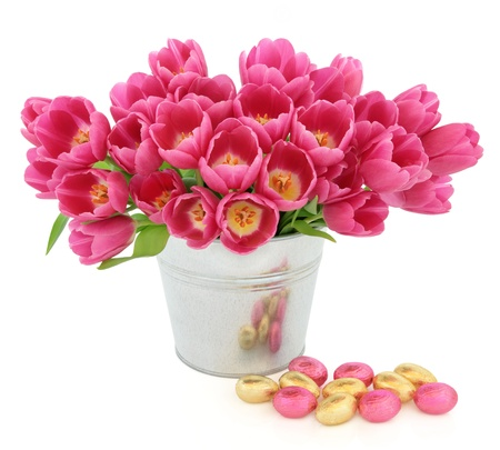 Easter egg group with pink tulip flowers in a metal vase over white background  Stock Photo - 17119656