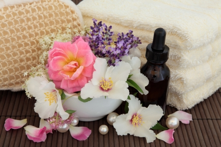 Spa still life of flower and herb leaf sprigs, cream towels, exfoliating scrub, aromatherapy essential oil bottle and pearls over brown bamboo  Stock Photo - 17248867