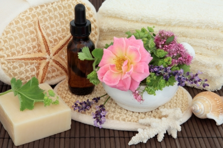 Spa arrangement of herb and flower leaf sprigs, cream towels, exfoliating  scrub, aromatherapy essential oil bottle, sea coral and natural soap over bamboo Stock Photo - 17248872