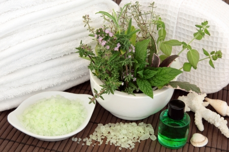 Herb and flower leaf sprigs in a mortar with pestle, bath crystals, shells, aromatherapy essential oil bottle, white towels and linen bath sponge over bamboo background  Stock Photo - 17248874
