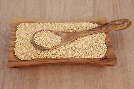 quinua: La quinua grano en un taz�n y una cuchara de madera de olivo sobre fondo papiro