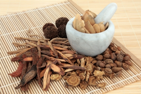Chinese herbal medicine selection in a marble mortar with pestle and loose over bamboo mats  Stock Photo - 17248875